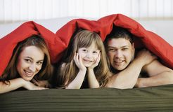Happy family relaxing in bed Stock Images