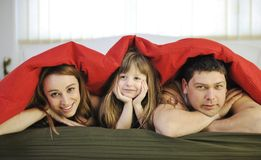 Happy family relaxing in bed. Happy young family at home relaxing in bed royalty free stock photo