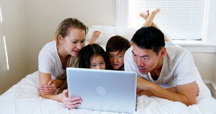 Happy family relaxing on bed and using laptop. In bedroom stock video footage