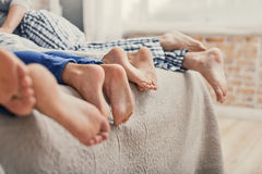 Happy family relaxing at home. Enjoying some family time. Close up of family showing off four feet and lying on bed in morning royalty free stock image