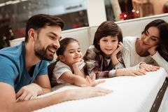 Happy family is relaxing on mattress in orthopedic furniture store. Big family check softness of mattress royalty free stock photos