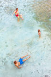 Happy family relaxing in natural sea pool stock image