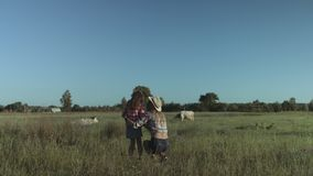 Happy family relaxing in nature in countryside. Lovely mother and cute elementary age daughter smelling wild flowers and spending great time together in stock footage