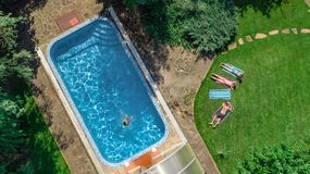 Happy family relaxing by swimming pool, aerial drone view from above of parents and kids have fun on vacation, family weekend royalty free stock image