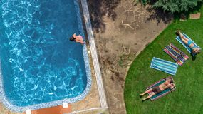 Happy family relaxing by swimming pool, aerial drone view from above of parents and kids have fun on vacation, family weekend. On resort stock photography