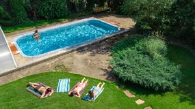 Happy family relaxing by swimming pool, aerial drone view from above of parents and kids have fun on vacation, family weekend. On resort stock photos