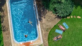Happy family relaxing by swimming pool, aerial drone view from above of parents and kids have fun on vacation, family weekend. On resort stock images