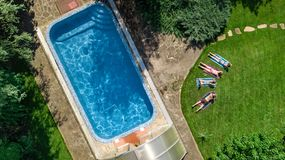 Happy family relaxing by swimming pool, aerial drone view from above of parents and kids have fun on vacation, family weekend. On resort stock photo