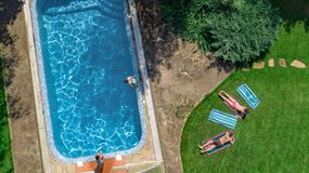 Happy family relaxing by swimming pool, aerial drone view from above of parents and kids have fun on vacation, family weekend royalty free stock photos