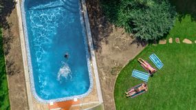 Happy family relaxing by swimming pool, aerial drone view from above of parents and kids have fun on vacation, family weekend. On resort royalty free stock images