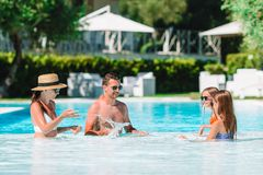Happy family of four in outdoors swimming pool stock images