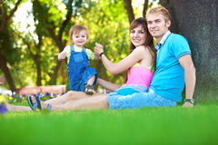 Happy family are resting in the green summer park Royalty Free Stock Image