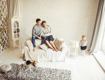 Happy family resting in the living room on Sunday. Young family resting in living room on Sunday Royalty Free Stock Image