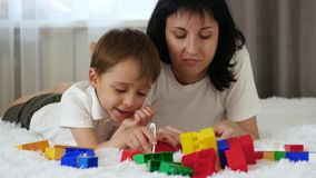 Happy family resting lying on the bed. Mother and child play, building of colored blocks.