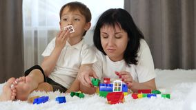 Happy family resting lying on the bed. Mother and child play, building of colored blocks. Mom kisses her baby.
