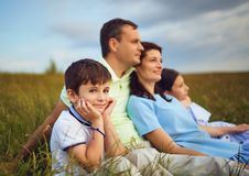 Family resting together sitting on grass in nature. stock images