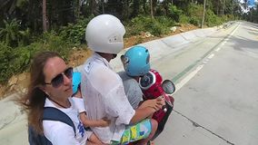 A happy family rides a motorbike in the tropics stock footage