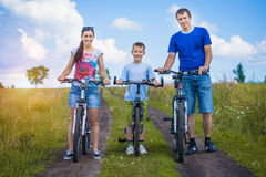 Happy family are riding bicycle in the field Royalty Free Stock Image