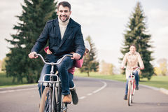 Happy family riding bicycles in park Stock Photo
