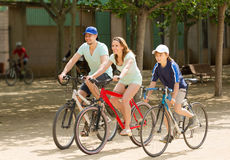 Happy family riding bicycles in park togetherness Stock Photos