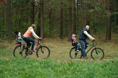 Happy family riding bike in wood Stock Photo