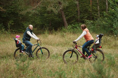 Happy family riding bike in wood Royalty Free Stock Photo