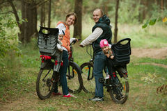 Happy family riding bike in wood Royalty Free Stock Photos