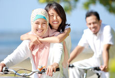 Happy family riding bikes. Happy muslim family riding bikes together in beautiful sunny day Stock Image