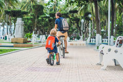 Happy family is riding bikes outdoors and smiling. Father on a b. Ike and son on a balancebike Stock Photos