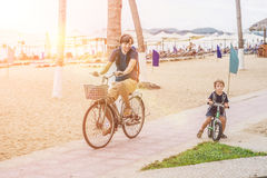 Happy family is riding bikes outdoors and smiling. Father on a b Stock Images
