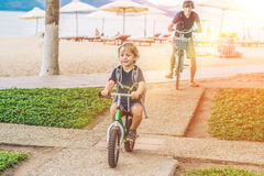 Happy family is riding bikes outdoors and smiling. Father on a b Royalty Free Stock Image