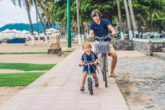 Happy family is riding bikes outdoors and smiling. Father on a b. Ike and son on a balancebike Royalty Free Stock Image