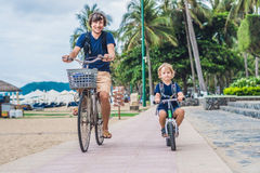 Happy family is riding bikes outdoors and smiling. Father on a b. Ike and son on a balancebike Stock Photo