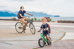 Happy family is riding bikes outdoors and smiling. Father on a b Royalty Free Stock Photography