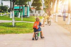 Happy family is riding bikes outdoors and smiling. Father on a b. Ike and son on a balancebike Stock Images