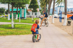 Happy family is riding bikes outdoors and smiling. Father on a b. Ike and son on a balancebike Stock Image