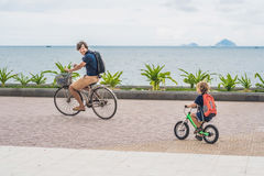 Happy family is riding bikes outdoors and smiling. Father on a b. Ike and son on a balancebike Royalty Free Stock Photo