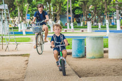 Happy family is riding bikes outdoors and smiling. Father on a b. Ike and son on a balancebike Royalty Free Stock Photos
