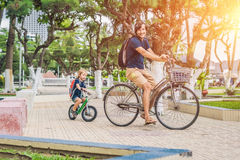 Happy family is riding bikes outdoors and smiling. Father on a b. Ike and son on a balancebike Royalty Free Stock Photography