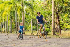 Happy family is riding bikes outdoors and smiling. Father on a bike and son on a balancebike stock photography