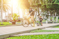 Happy family is riding bikes outdoors and smiling. Father on a b stock photo