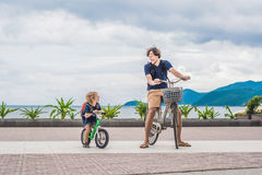 Happy family is riding bikes outdoors and smiling. Father on a b. Ike and son on a balancebike royalty free stock images