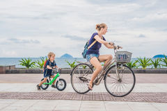 Happy family is riding bikes outdoors and smiling. Mom on a bike Stock Photos