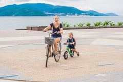 Happy family is riding bikes outdoors and smiling. Mom on a bike Stock Photo