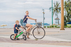Happy family is riding bikes outdoors and smiling. Mom on a bike. And son on a balancebike Royalty Free Stock Image