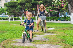 Happy family is riding bikes outdoors and smiling. Mom on a bike. And son on a balancebike Stock Photo