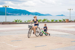 Happy family is riding bikes outdoors and smiling. Mom on a bike. And son on a balancebike Stock Photography