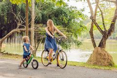 Happy family is riding bikes outdoors and smiling. Mom on a bike stock images