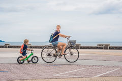 Happy family is riding bikes outdoors and smiling. Mom on a bike Stock Photography