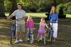 Happy Family Riding Bikes In A Park. A young family with mother father and two blond daughters riding their bikes in a sun bathed green park Royalty Free Stock Images